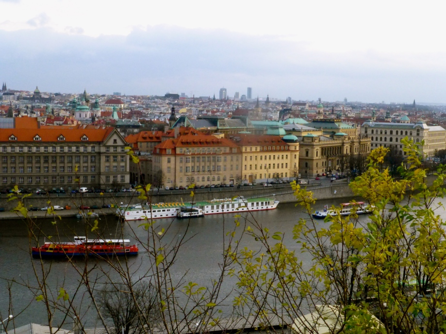 Prague - River flanked by rows of grossly grand blocks.  Painted soft orange, deep yellow, soft green or cream - all sporting the uniform red-clay roof tiles.